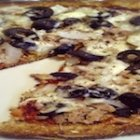 Cauliflower Pizza Crust Recipe Topped with Black Olives and Organic Turkey