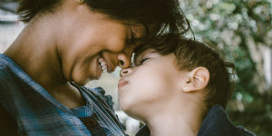 mom smiling with her face close to her son's