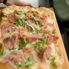 Pizza with prosciutto, parmigiano-reggiano and arugula