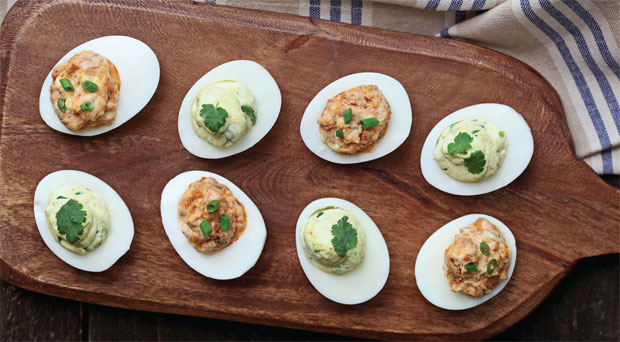 plate of deviled eggs with different garnishes
