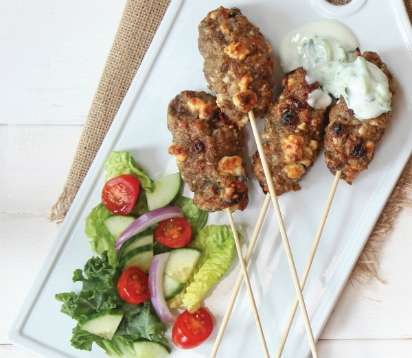 meat on a stick with a side salad and dip