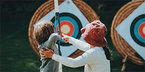 mom helping son shoot a bow and arrow