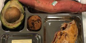 bento box with whole sweet potato and overly ripe avocado