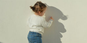 little girl facing the wall
