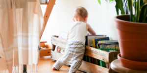 baby standing by a crate of books
