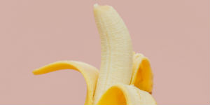 peeled banana on a pink background