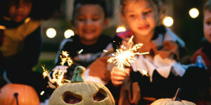 kids dressed in costumes with sparklers and jack-o-lanters