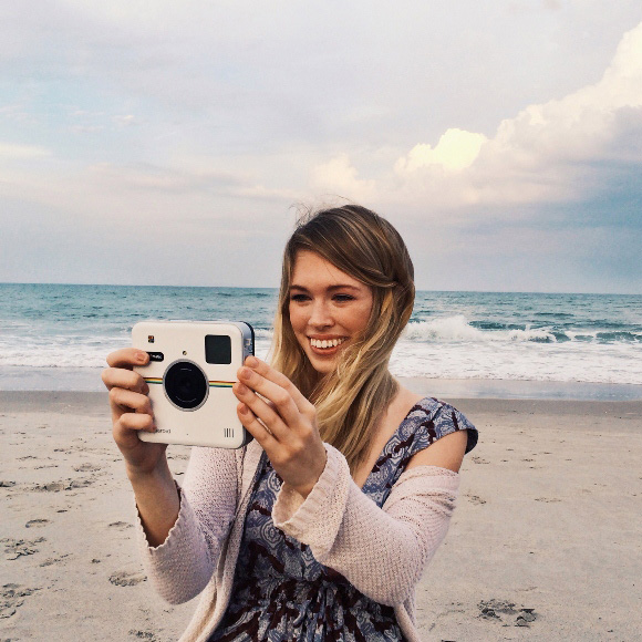 girl using Polaroid camera at the beach