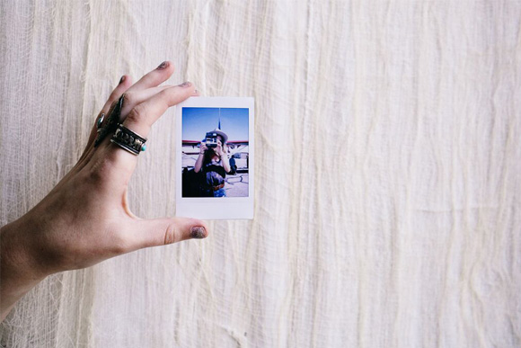 holding a Polaroid photo