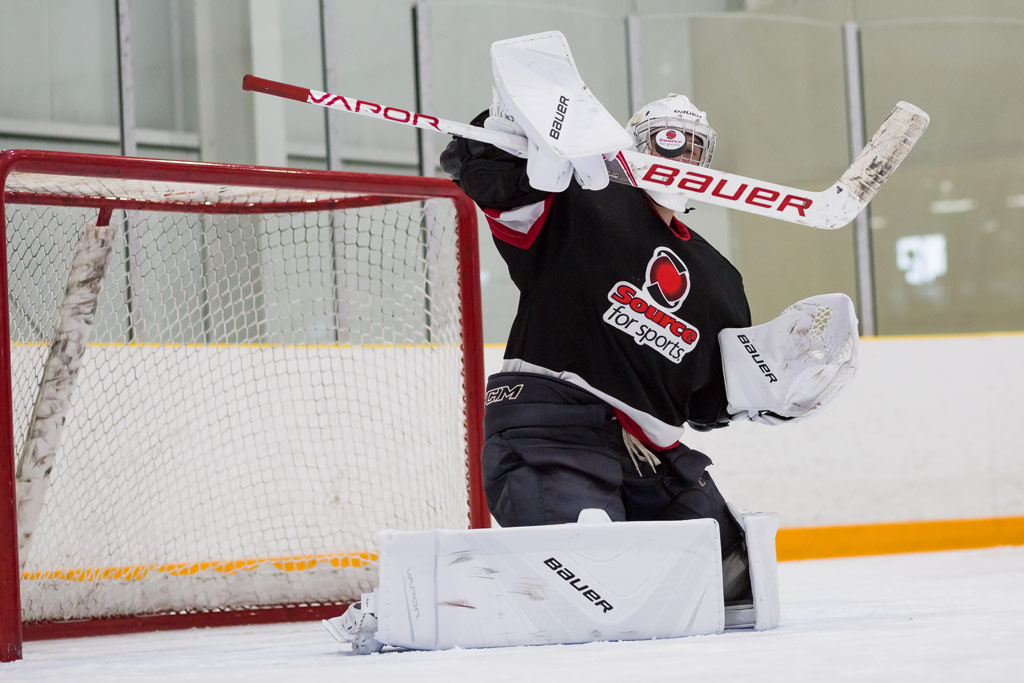 Goalie wearing BAUER Vapor 1X OD1N goalie pads and gear making a save during a hockey game.