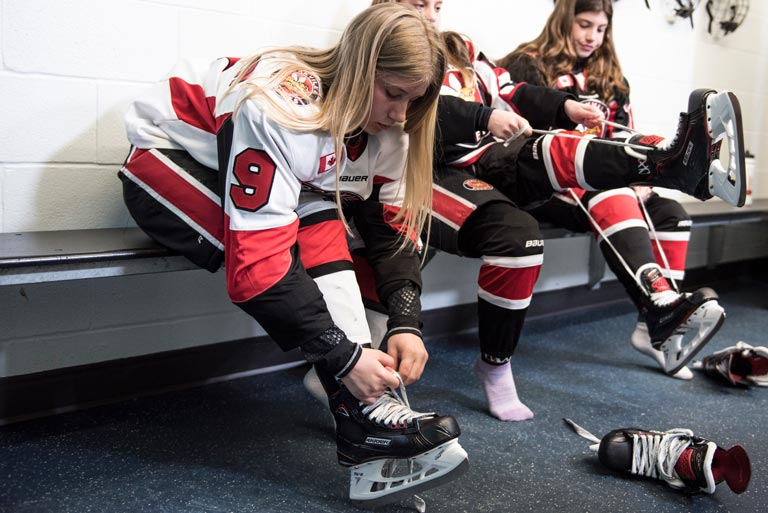 Girls tying up their Bauer Vapor skates in a hockey dressing room before the game.