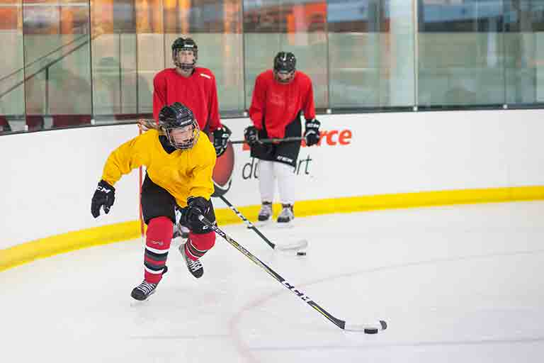 Girls hockey player skating with the puck as drills take place in Calgary, Alberta.