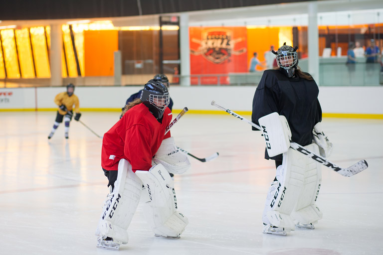 Girls talking on the ice dressed in goalie gear.