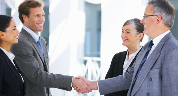 Photo of business men and women shaking hands