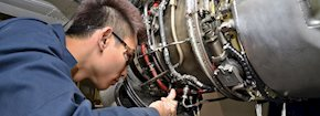 Student working on a plane engine