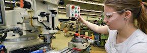 Female student working with machining equipment