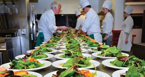 Group of students and a chef making salads