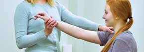 Woman performing physiotherapy treatment on arm of patient