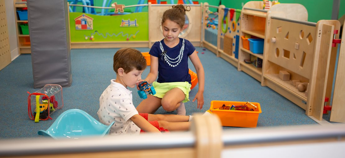 Enclosed toddler area with developmentally appropriate manipulatives and toys
