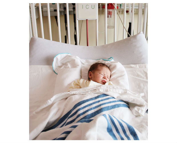 baby in a hospital bed with a blanket