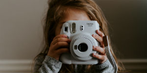 girl holding a camera to her face