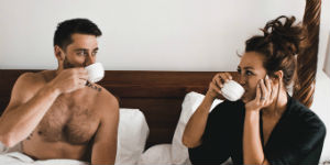 man and woman in bed drinking coffee