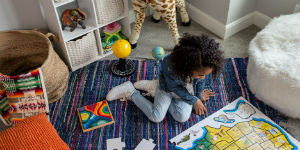 girl playing with a puzzle on the floor