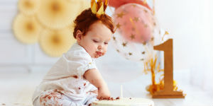 little boy with balloons and cake