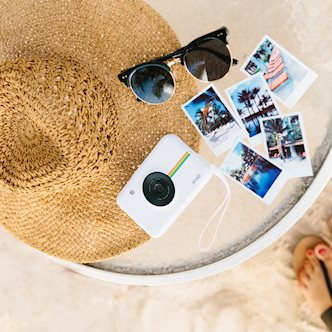 Overhead view of Polaroid travel photos on a round glass table next to sunglasses, a Polaroid Snap, and a sun hat