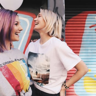 Two women smiling in front of a metal garage door wearing Polaroid and Esprit apparel