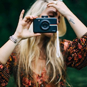 Blonde woman in red floral shirt using Polaroid Snap