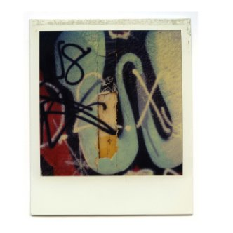 Polaroid photo of graffiti and other street art on a wall with exposed wood underneath