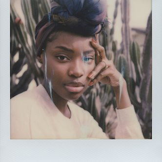 Polaroid photo of a female model wearing a headscarf, posing in front of cacti