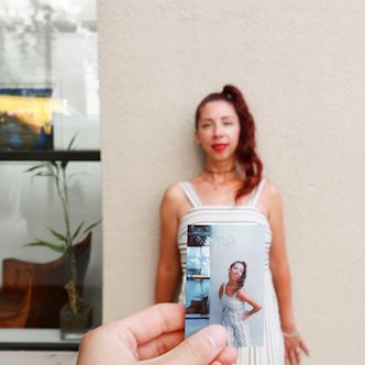 Mimi Perez, real estate agent, standing behind a Polaroid photo of herself posing