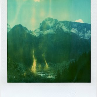 Mountain landscape take with expired Polaroid SX-70 film with blueish hues and yellow flame-like streaks