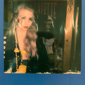 "Polaroid OneStep 2 photo of a woman in a black jacket in front a window labeled ""Lafayette"""