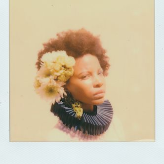 Polaroid portrait shot of a female model wearing white flowers in her hair and a blue ruffled collar