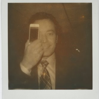 Polaroid photo of Jimmy Fallon holding a cell phone in front of his face