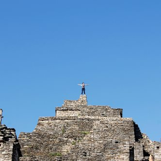Person with hands outstretched, standing at the top of ancient stone city ruins