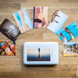 Polaroid photos arranged in a semicircle around a Polaroid Zip Instant Printer
