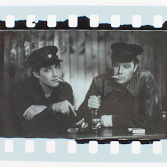 Black and white film photo of two men in leather jackets and police caps smoking cigarettes and drinking Russian beer