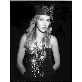 Black and white Polaroid photo of a female model wearing a strapless sequin dress and a ribbon on her head