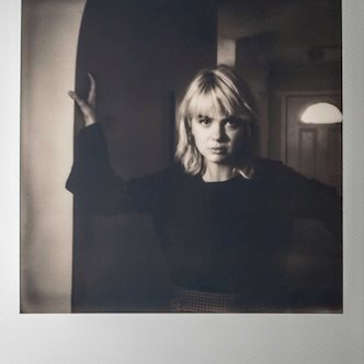 Black and white Polaroid photo of Madi Clark posing in a hallway
