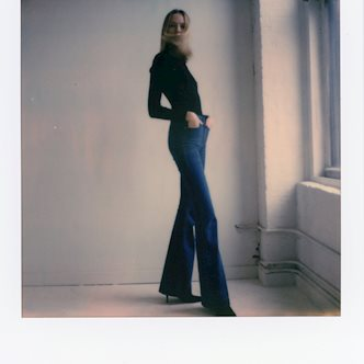 Female model wearing a black turtleneck and navy denim jeans posing in front of a white wall