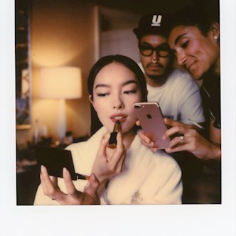 Polaroid photo of Fei Fei Sun applying make up with her assistants in the background