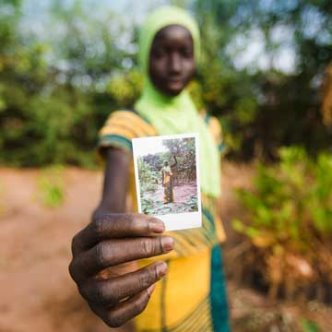 Senegalese woman in a yellow headdress holding a Polaroid photo of herself