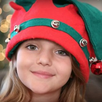 Young girl wearing a red Christmas elf hat with jingle bells on it
