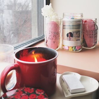 Mason jars full of candy, flowers, and Polaroid photos behind a candle and a heart-shaped dish