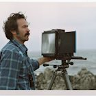 Actor, photographer, and skateboarder Jason Lee by the coastline with a Polaroid camera