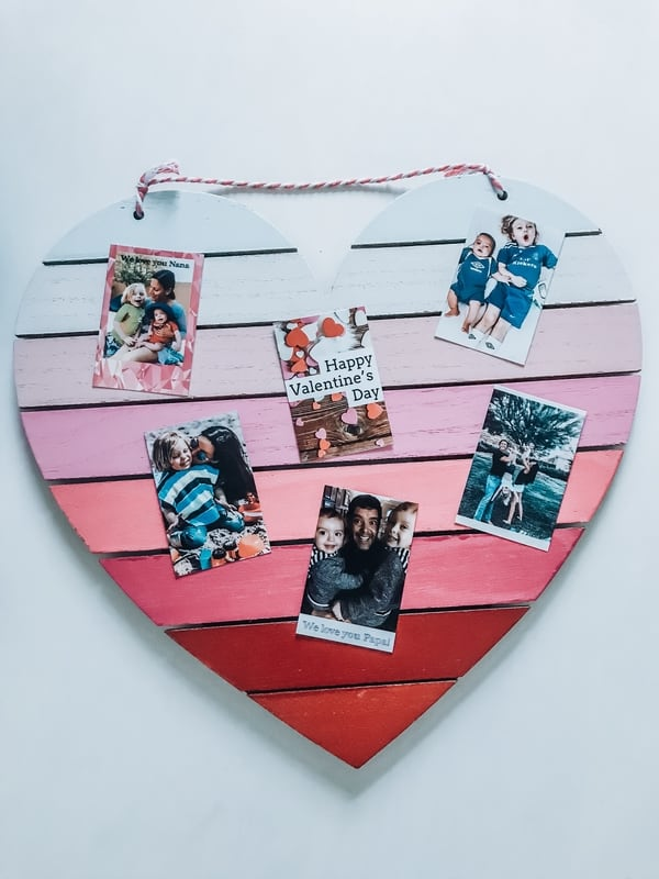 A collage Polaroid photos of different families on a Valetine's Day themed pink wooden heart